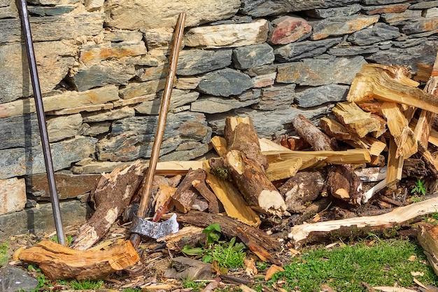 Een houten bijl en een metalen stok in de buurt van een stenen muur en gehakt brandhout