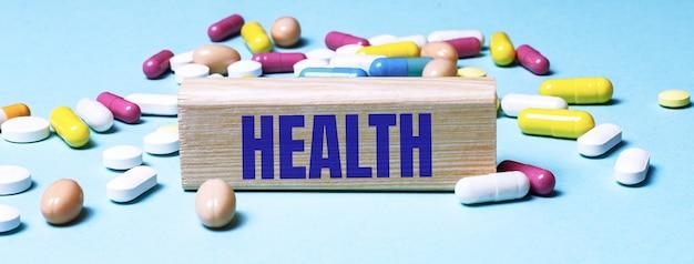 Een houten blok met het woord gezondheid staat op een blauwe ondergrond tussen veelkleurige pillen