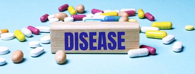 Een houten blok met het woord ziekte staat op een blauwe ondergrond tussen veelkleurige pillen