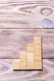Een houten blokken kubus over zwarte houten textuur