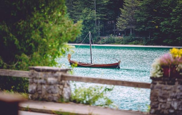 Een houten boot op het water omgeven door groen onder het zonlicht