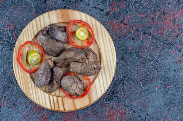 Een houten bord kippenkotelet met gesneden tomaat.