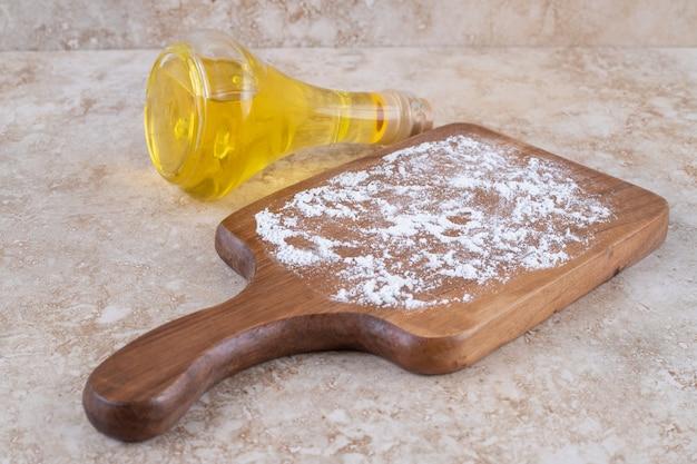 Een houten bord met bloem en een glazen fles olie