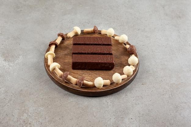 Een houten bord met chocolaatjes en een houten kom met zoete champignons.