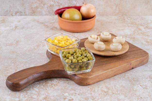 Een houten bord met diverse groenten op een marmeren ondergrond