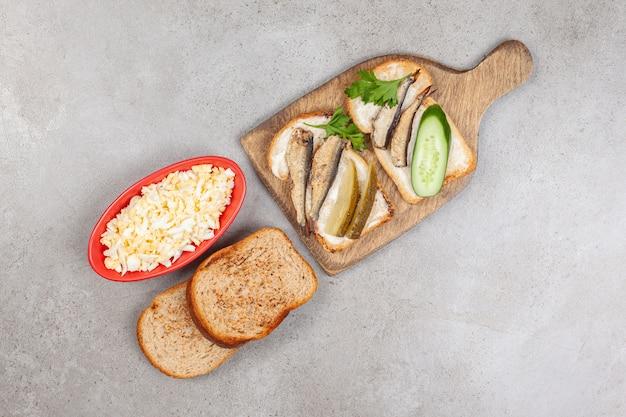 Een houten bord met gebakken toast en sprot