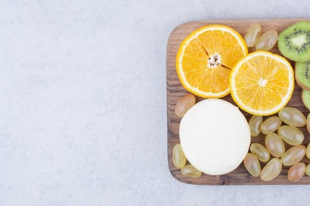 Een houten bord met gesneden kaas en fruit. hoge kwaliteit foto