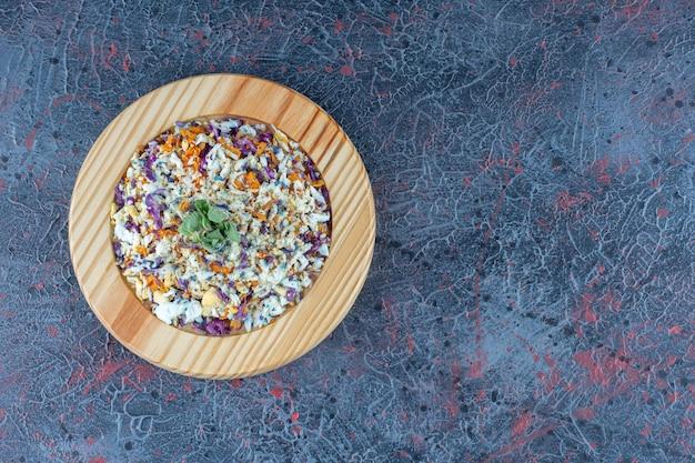 Een houten bord met groentesalade op marmeren ondergrond