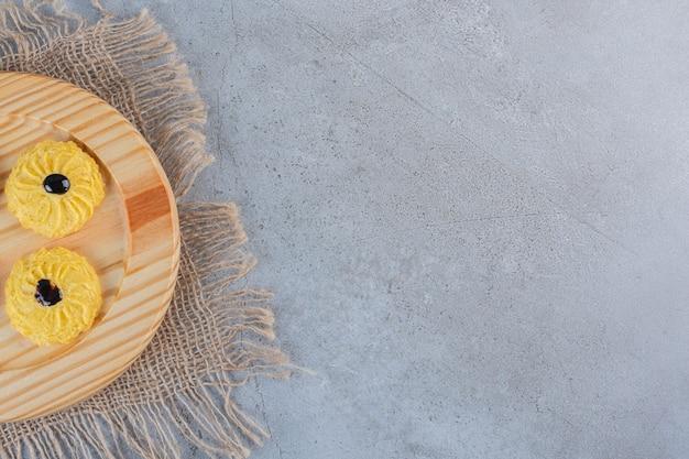 Een houten bord met heerlijk rond koekje op stenen ondergrond.