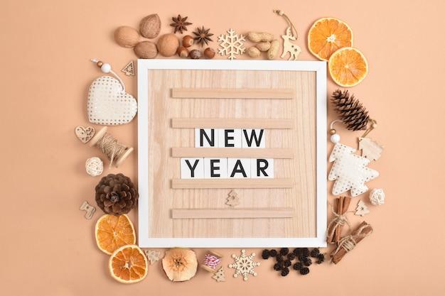 Een houten bord met het opschrift nieuwjaar naast eco-decoraties voor ecodesign.