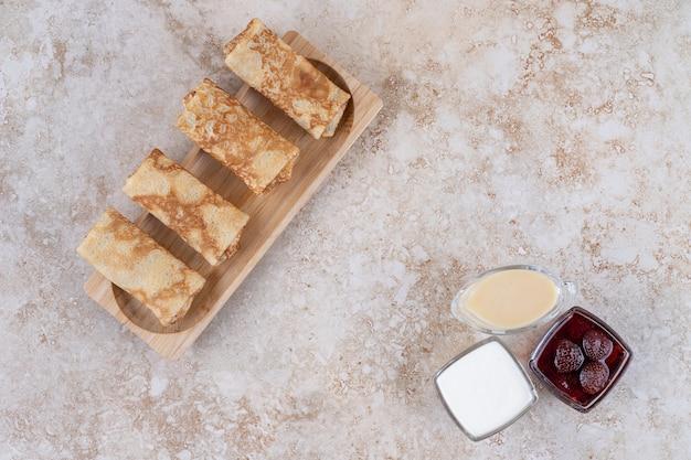 Een houten bord met lekkere pannenkoeken en aardbeienjam