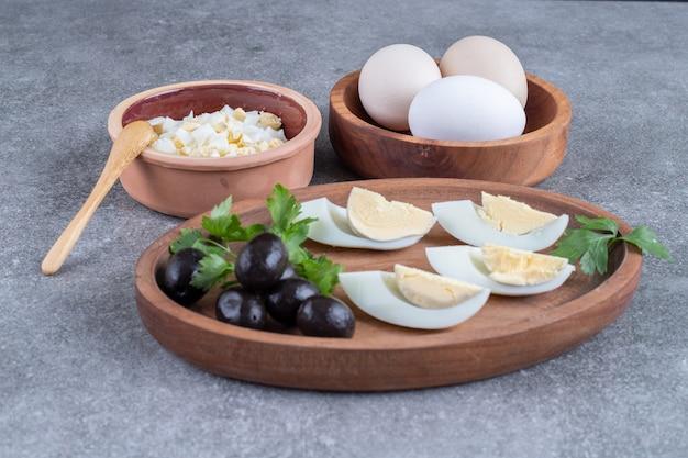Een houten bord met olijven en gekookte eieren. hoge kwaliteit foto
