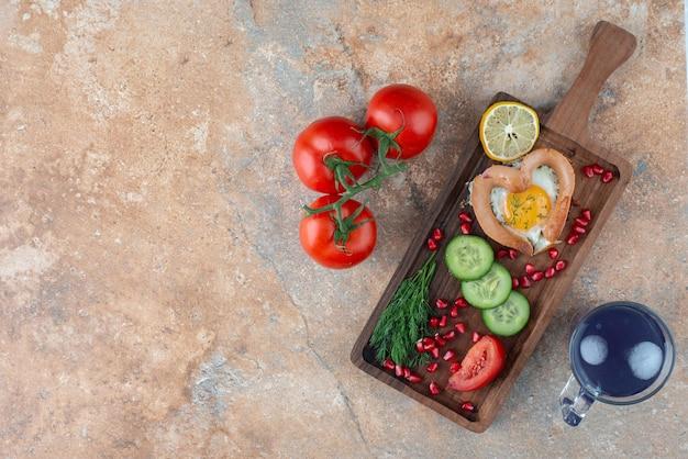 Een houten bord met omelet en groenten met kopje drank.