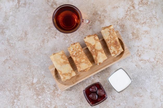 Een houten bord met pannenkoeken en een kopje thee