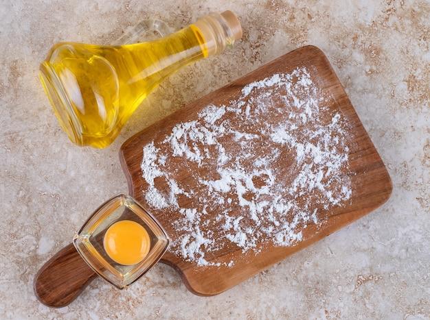 Een houten bord met rauwe dooier en een glazen fles olie