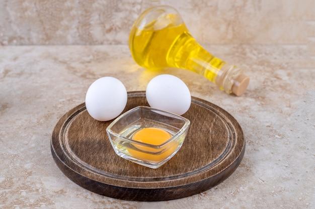 Een houten bord met rauwe eieren en een glazen fles olie