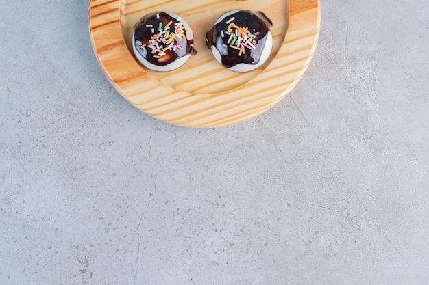 Een houten bord met smakelijke geglazuurde koekjes op steen.