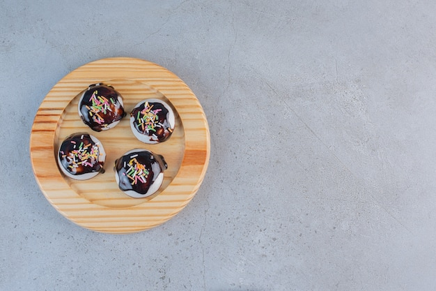 Een houten bord met smakelijke geglazuurde koekjes op stenen tafel.