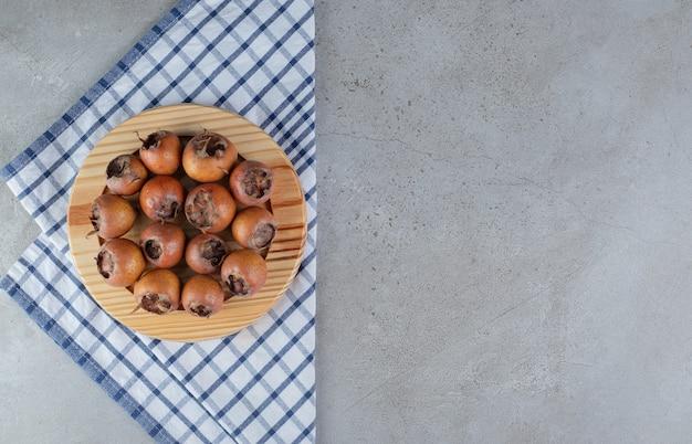 Een houten bord met verse, sappige kaki op een zak. hoge kwaliteit foto