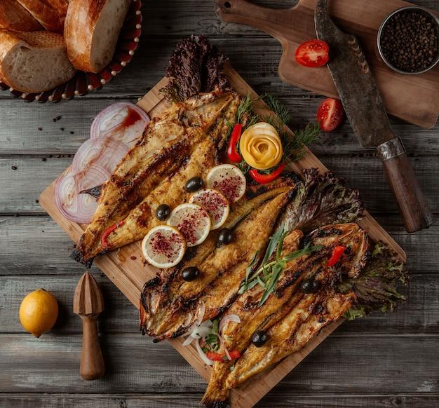 Een houten bord met visgrills en kruiden erop