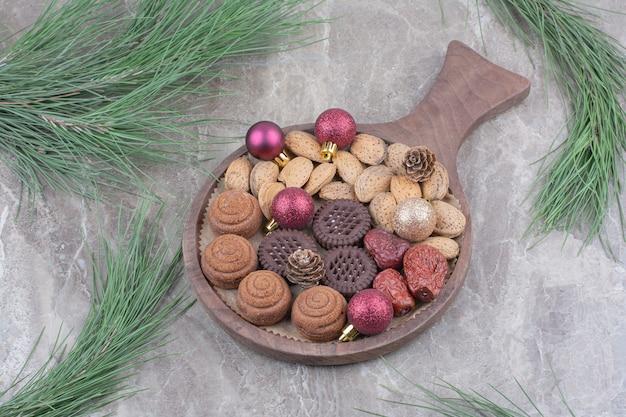 Een houten bord van amandelen en koekjes op marmeren achtergrond.