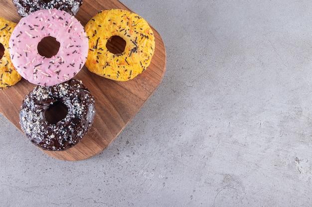 Een houten bord van donuts met chocolade en gele coating