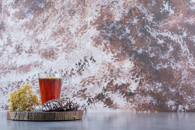 Een houten bord van een glazen kopje hete thee met koekjes en mimosa bloem