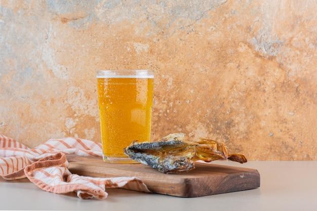 Een houten bord van gedroogde vis met een glazen mok bier op een witte achtergrond.