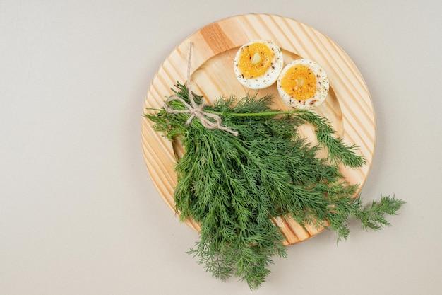 Een houten bord van gekookt ei met kruiden en groenten.