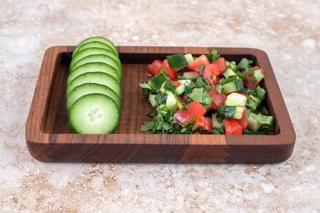 Een houten bord van gemengde groentesalade en gehakte komkommer.