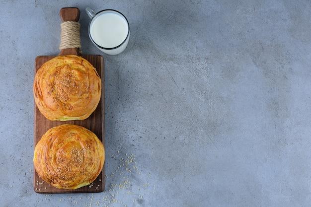 Een houten bord van nationaal gebak van azerbeidzjan met een glazen kopje verse melk