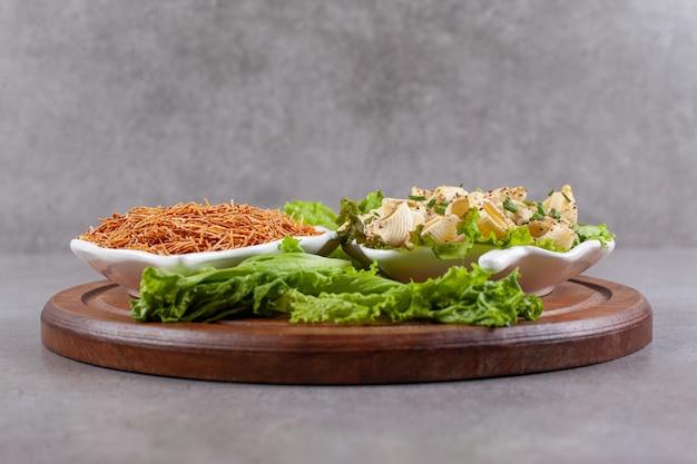 Een houten bord van rauwe macaroni met sla en greens