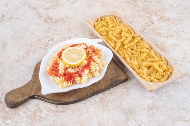 Een houten bord van rauwe spiraalvormige macaroni en groenten