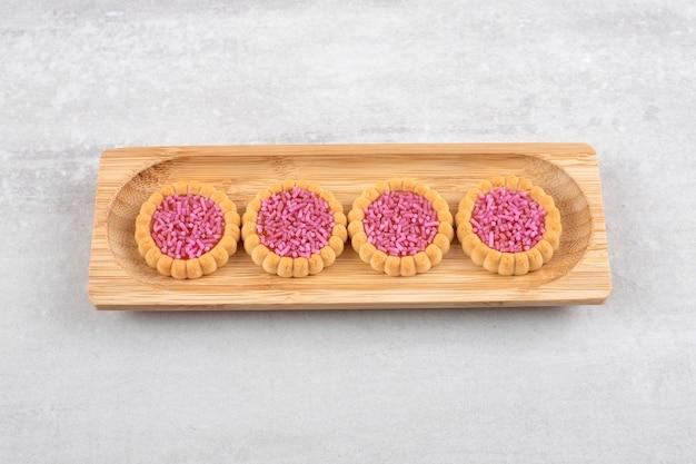 Een houten bord van zoete koekjes met hagelslag in gat op een stenen oppervlak.