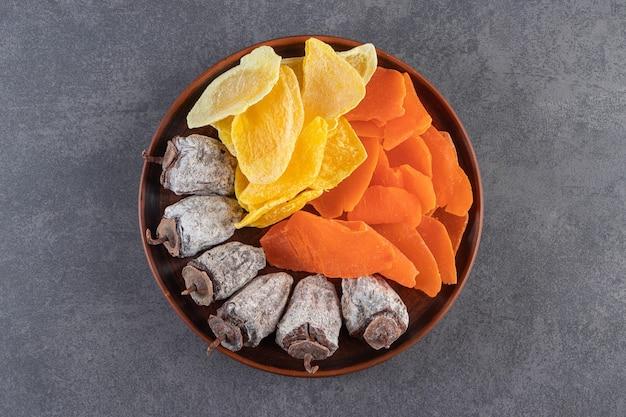 Een houten bord vol gemengd gezond gedroogd fruit op stenen tafel.