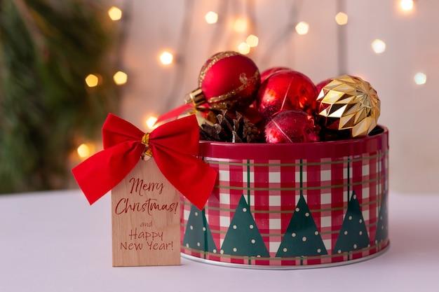 Een houten briefje met rode strik en tekst prettige kerstdagen en gelukkig nieuwjaar een ronde blikken doos speelgoedballen