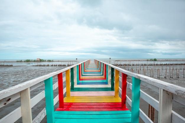 Een houten brug die uitsteekt in de zee
