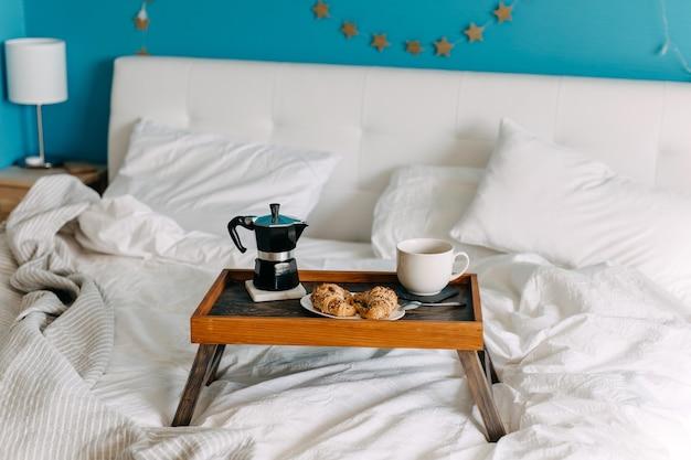 Een houten dienblad met croissants en kopje koffie op bed