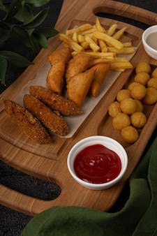 Een houten dienblad met frietklompjes en een aardappelsnack