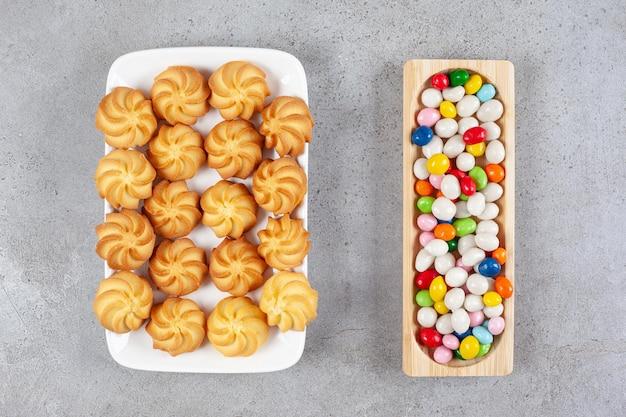 Een houten dienblad met snoepjes naast een witte plaat met koekjes op een marmeren oppervlak.