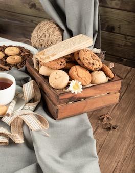 Een houten dienblad van koekjes en crackers met een kopje thee