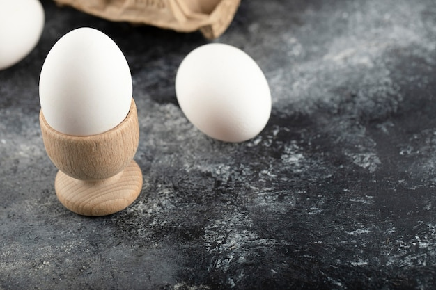 Een houten eierdopje met gekookt kippenei.