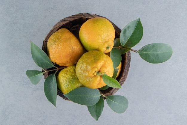 Een houten emmer gevuld met mandarijnen en bladeren op marmer.