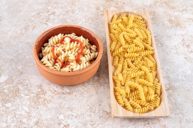 Een houten en klei kommen met heerlijke pasta op een marmeren ondergrond