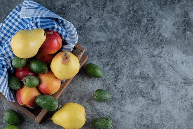 Een houten fruitschaal vol met peren, feijoa's en perziken