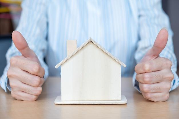 Een houten huis op de tafel en duimen omhoog. het bedrijfseigendom verkopen en het concept van de landgoedinvestering.