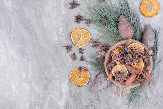 Een houten kerstbeker met stukjes sinaasappel, anijs en kaneel.