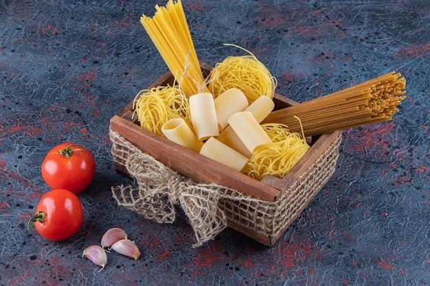 Een houten kist rauwe noedels met verse rode tomaten en knoflook op een donkere ondergrond.