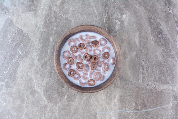Een houten kom chocolade gezonde granen ringen voor het ontbijt.