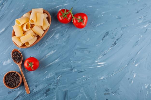 Een houten kom droge ruwe buisdeegwaren met verse rode tomaten en kruiden op een blauwe lijst.